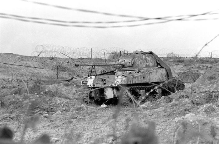 A right rear view of a wrecked and stripped Israeli Sherman Firefly tank with its gun turret traversed to the rear.
