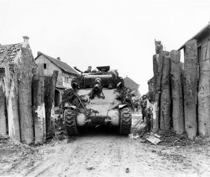 Camouflaged with evergreen boughs, tanks of the 1st Infantry Division (745th Tank Battalion), U.S. First Army, rolls through former German block in Gladbach, Germany.