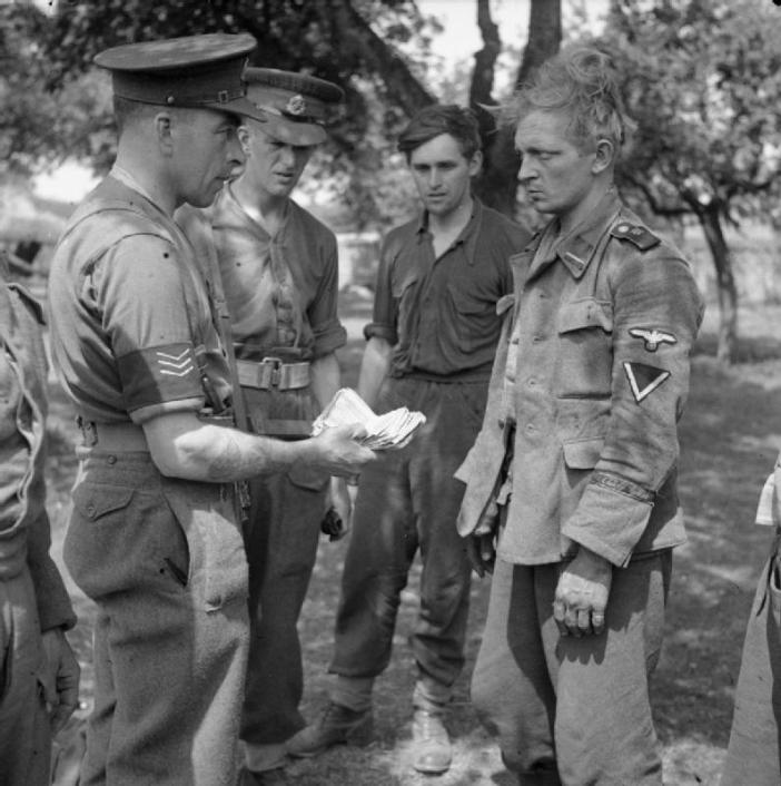 MPs question a German prisoner who was found to be carrying a large quantity of Russian banknotes, 20 July 1944.