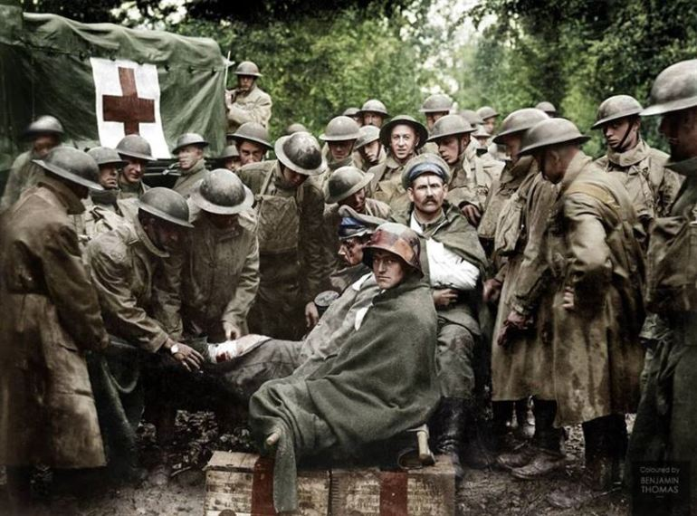 American medics of the 103rd and 104th Ambulance Companies give medical attention to wounded German prisoners.