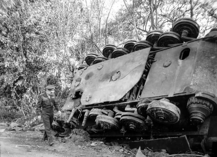 Dwight D. Eisenhower walking past a destroyed German Tiger Tank after the battle of Chambois, France 1944.