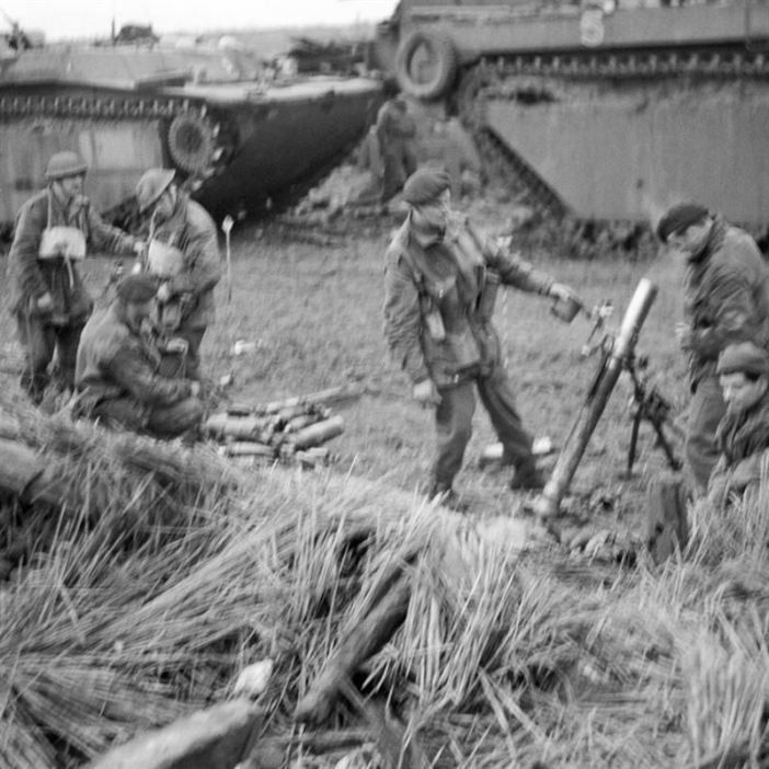 """3"""" mortars in action from behind the cover of amphibious tanks."""