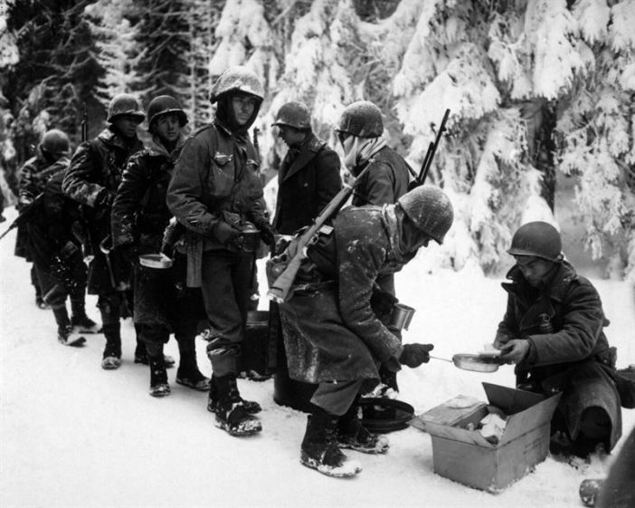 Chow is served to American infantrymen of the 347th Infantry Regiment on their way to La Roche, Belgium, 13 January 1945.