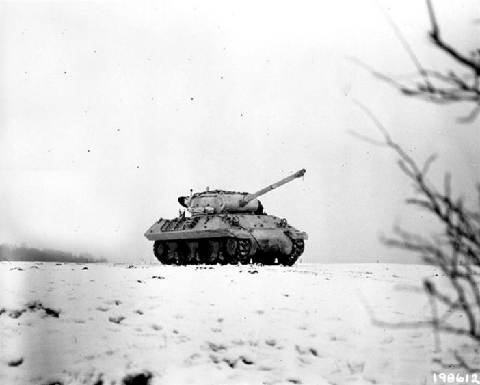 Battle of the bulge - Dudelange, Luxembourg. Painted white to blend with snow-covered terrain, an M-36 tank destroyer crosses a field. (3 Jan 1945)