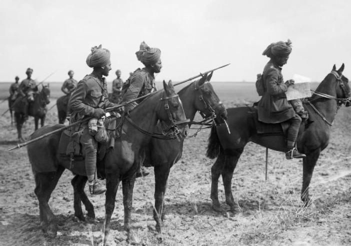Forward scouts of the 9th Hodson's Horse, an Indian cavalry regiment, pause to consult a map, near Vraignes, France. (Credits: Imperial War Museum)