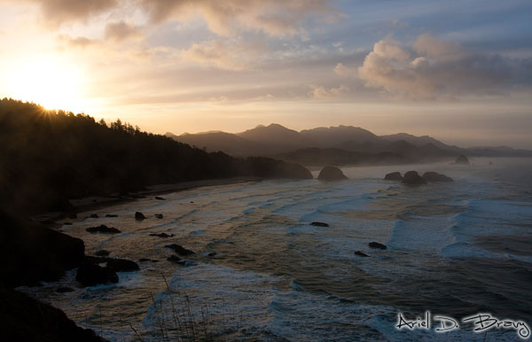 The sun peeks above the mountains at Ecola