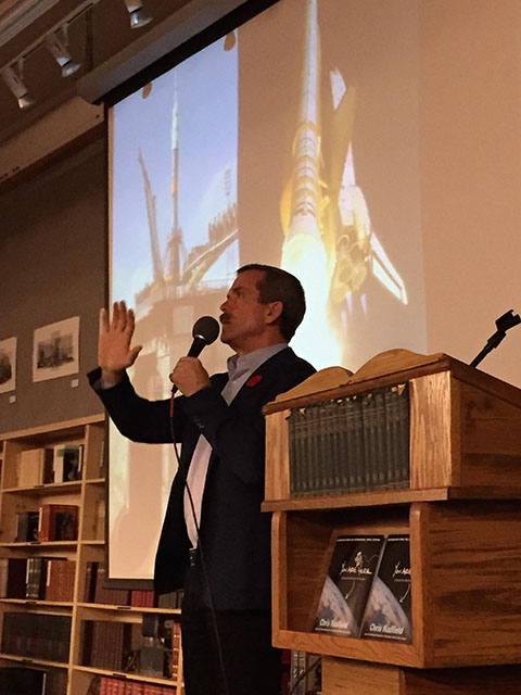 Chris Hadfield speaking in front of the Space Shuttle and Soyuz