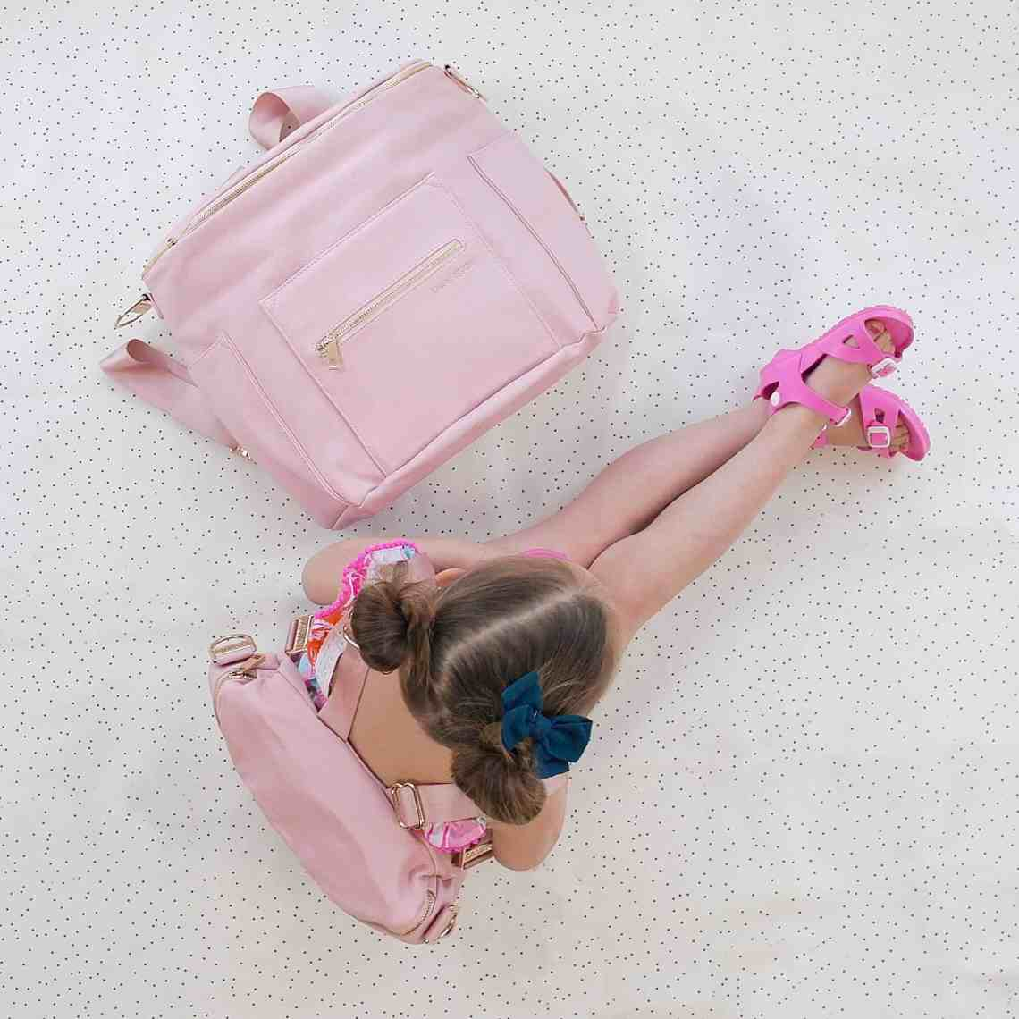 little girl with pink backpack next to pink diaper bag