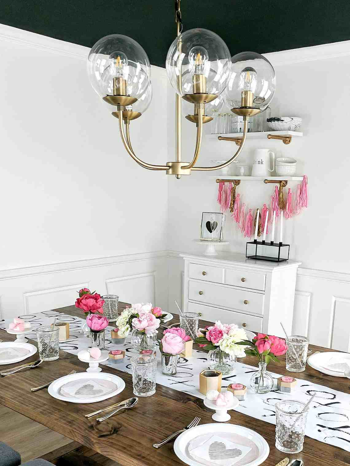 white room with gold chandelier and floral tablesetting