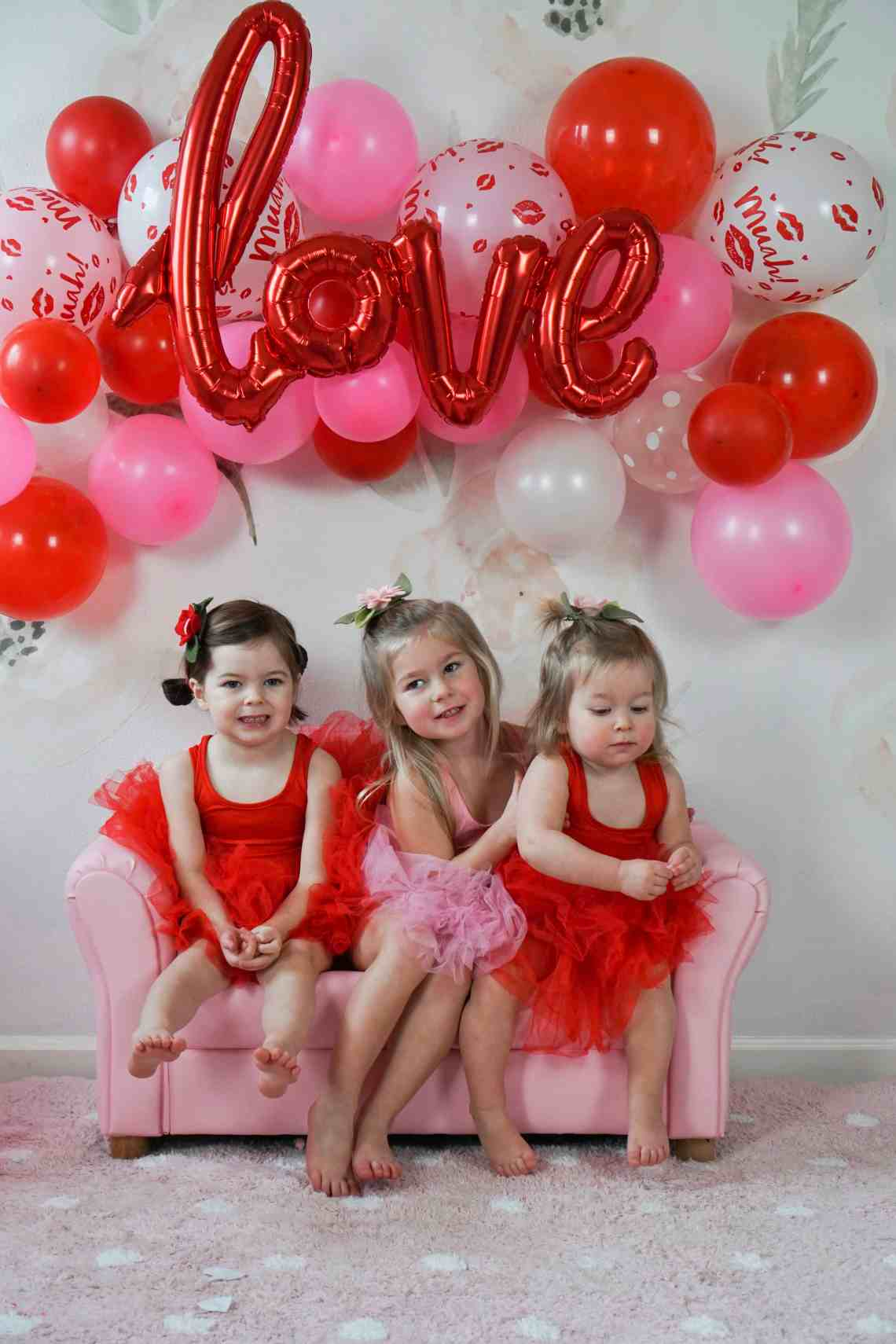 three toddler girls on pink couch in front of balloon wall