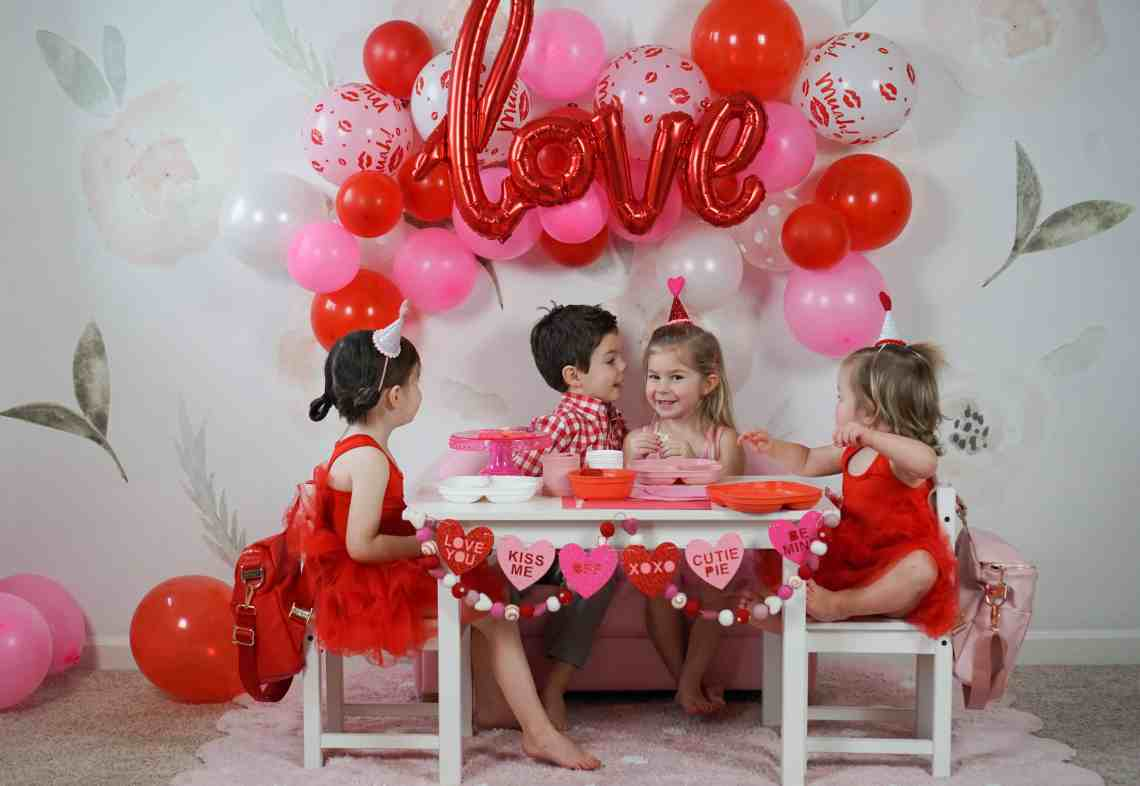 toddlers in front of pink and red balloons at white decorated table for valentines day