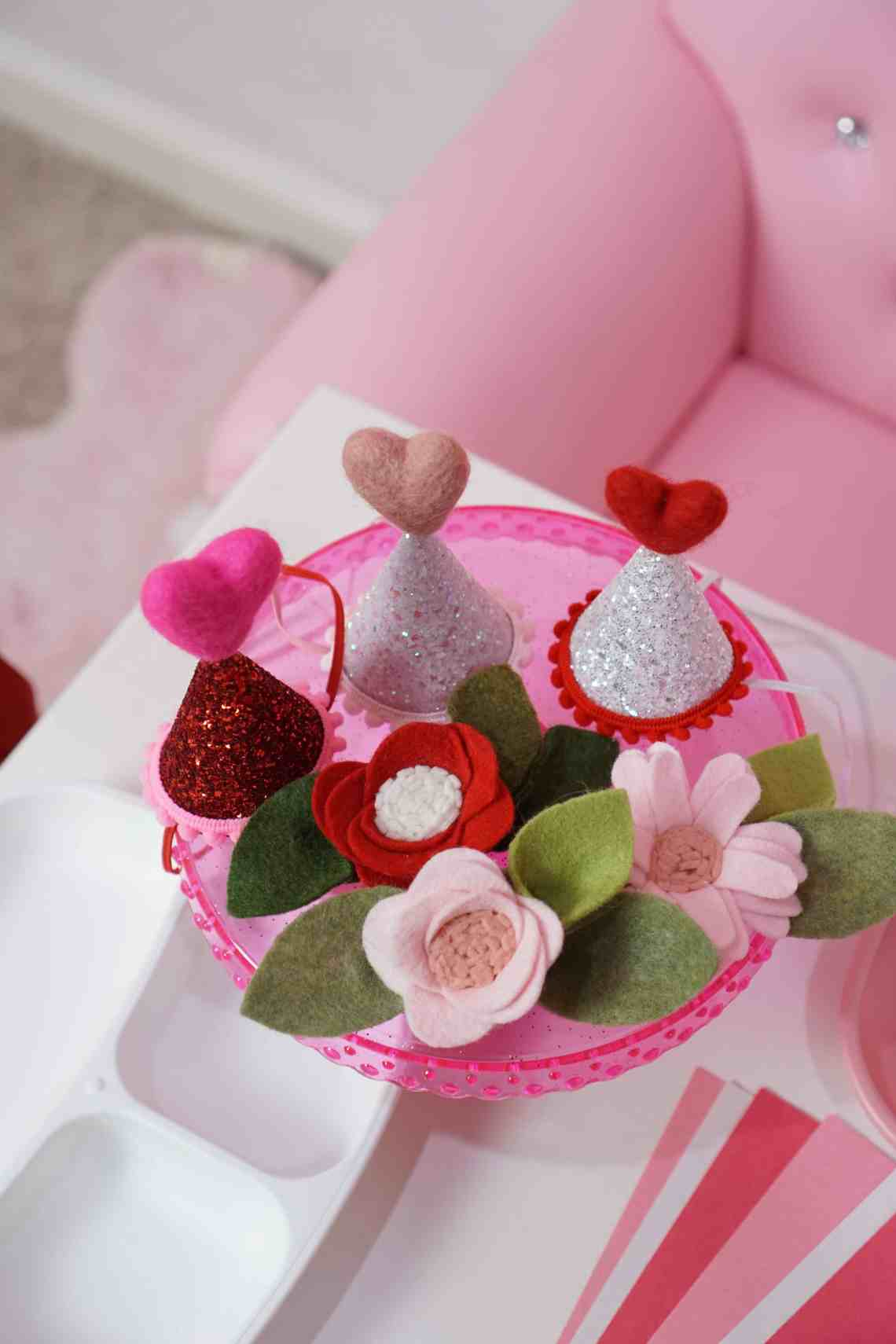 mini heart party hats and flower bows on a pink cake stand