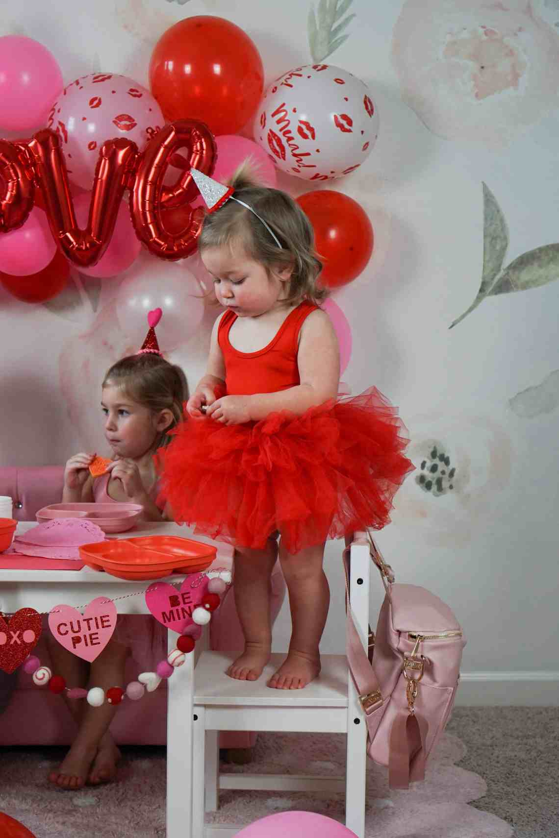 toddler girl in red tutu standing on chair