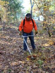 Gordon King of Norfork knocks down weeds with a gas-powered trimmer on Dogwood Trail in Lakeview.