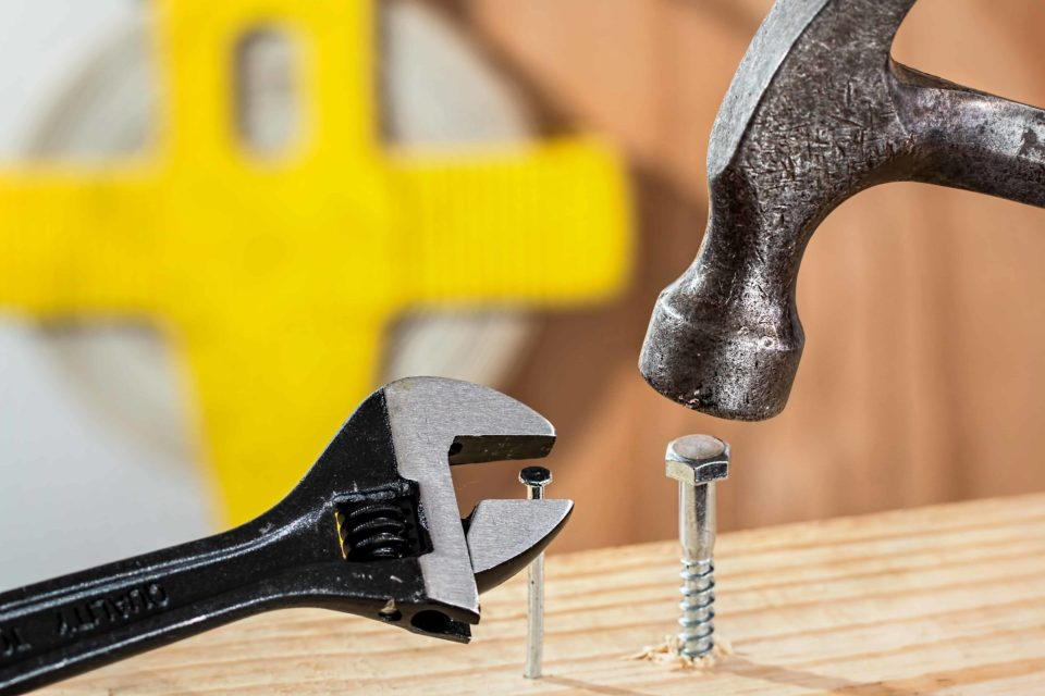 A wrench and a hammer are used to work on the nail and screw that are partially penetrating the piece of wood.