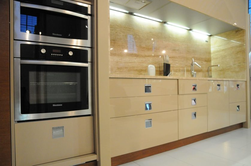 A modular kitchen cabinet maximizing storage space under the sink and another one under the oven. The appliance is purposefully placed there for efficiency.