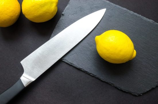 A knife is positioned beside the lemons for slicing; all of which sit on a dark counter-top.
