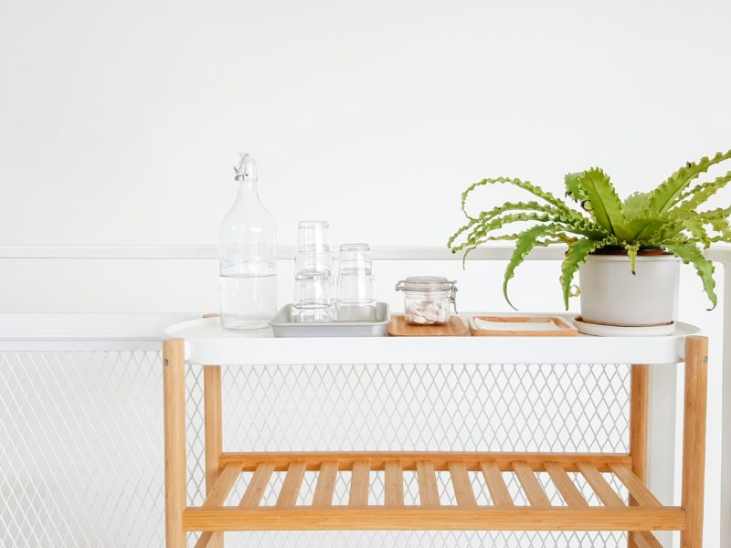 A cart with a bottle of water and a few glasses on a cart. The potted plant adds green to the white background.