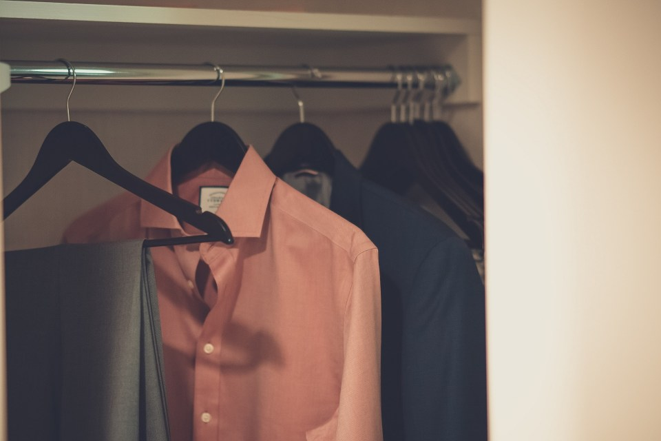 Men's button-up shirts and a pair of pants hanging on a rod. The cabinet has a lot of hanging space ideal for men's wardrobe.