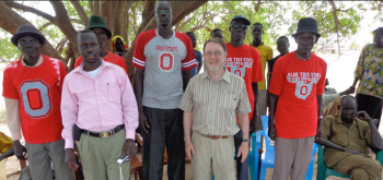 Jok Dau (second row, first from left) and Steve Walker (second row, second from left) are pictured with the leaders of Piol, South Sudan. The men are wearing Buckeye apparel that Walker and Aweng brought back to them.