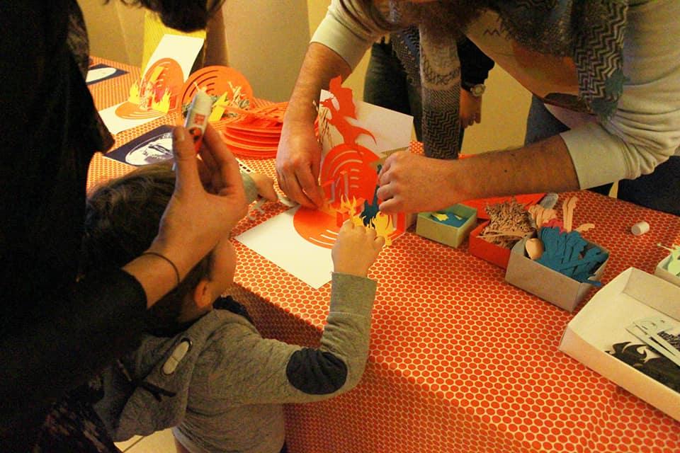Photo - un enfant réalise une oeuvre en papier découpé