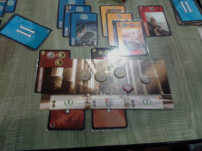 An up-close view of the Olympia wonder board. As a player builds the wonder in stages, cards are placed under the bottom edge of the board, indicating they were used to build the wonder instead of other buildings. The top left corner of the wonder is where production cards stack up, indicating the resources available. Above the board are the buildings build (so far) in this city.<br /> Pardon the glare - the cards are sleeved and the lighting in the deli wasn't the best.