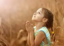Little girl looking to heaven while she prays