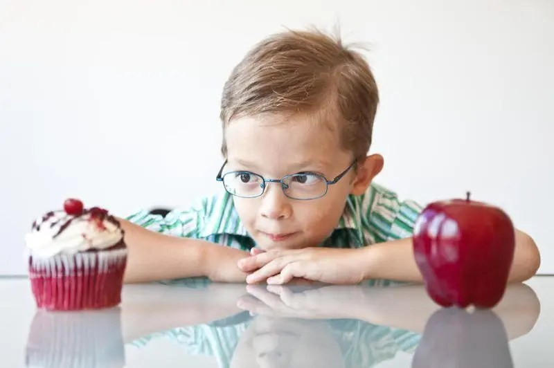 A little boy choosing between a cupcake and apple.