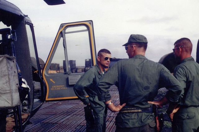 """U.S. Army Maj. Charles Kettles, standing beside his heavily damaged """"Huey"""" helicopter on return from the May 15, 1967, emergency extraction rescue operation."""
