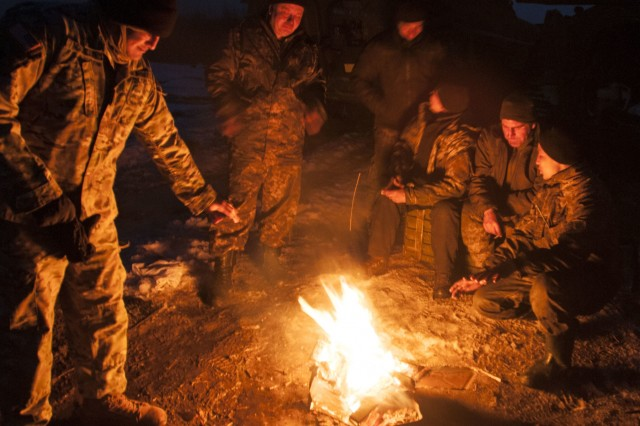Sgt. Joel Aguilar, a member of 1st Battalion, 179th Infantry Regiment, 45th Infantry Brigade Combat Team and a resident of Oklahoma City, joins a Ukrainian BMP-2 crew by a fire while they wait for their turn on the range for night fire familiarization at the International Peacekeeping and Security Center, near Yavoriv, Ukraine, on Feb. 16.