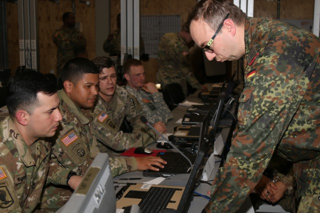 Grafenwhoer, Germany (March 3, 2017) - The 82nd Airborne Division Artillery's (82nd ABN DIVARTY) fire control element gives firing data to the German Artillery Systems Cooperation Activities liaison officer in the 82nd ABN DIVARTY tactical operations center here. Dynamic Front II is an artillery operability exercise taking place at the 7th Army Training Command's Grafenwoehr Training Area, Germany, Feb. 26 to March 10, 2017. (US Army photo by Staff Sgt. Kathleen V. Polanco)