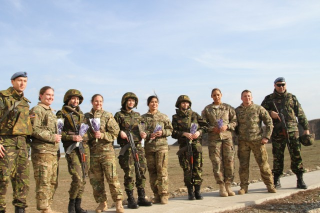 Soldiers from the Romanian and U.S. military gather upon completion of a ceremony commemorating International Women's Day, Mihail Kogalniceanu Air Base, March 8, 2017. The soldiers present were from the Fort Drum, N.Y.-based 2-10 Assault Helicopter Battalion, 10th Combat Aviation Brigade and the Romanian Military Police Company attached to the air base, and they had just participated in joint air assault training that featured UH-60 Black Hawk helicopters. The training exercise was part of Operation Atlantic Resolve, a multi-nation effort between the United States and her Allies and partners to enhance regional stability and deter aggression in eastern Europe. (U.S. Army photo by PV2 Nick Vidro, 7th Mobile Public Affairs Detachment)
