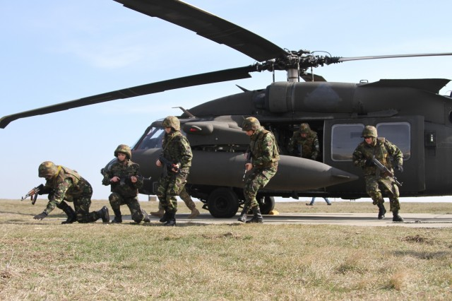 Dropping to the ground after exiting a UH-60 Black Hawk helicopter, Romanian Army soldiers assigned to the Military Police Company, Mihail Kogalniceanu Air Base, assume a defensive posture during air assault operations training, March 8, 2017. Along with U.S. Army Soldiers from the 2-10 Assault Helicopter Battalion, 10th Combat Aviation Brigade, the Romanians flew to a nearby location where numerous air assault techniques were practiced. The training is an integral part of Operation Atlantic Resolve, a multi-nation effort between the United States and her Allies and partners that significantly contributes to peace across eastern Europe by enhancing stability and deterring aggression. (U.S. Army photo by PV2 Nick Vidro, 7th Mobile Public Affairs Detachment)