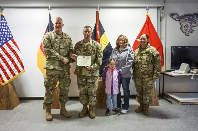 Maj. Gen. Timothy McGuire (left), Deputy Commanding General of U.S. Army Europe (USAREUR), U.S. Army Sgt. 1st Class Anthony S. Buchheit (CTR), an infantry Soldier with the Timberwolves Observer, Coach, Trainer (OCT) Team, Joint Multinational Readiness Center, his family and Command Sgt. Maj. Sheryl Lyons (right), USAREUR Command Sergeant Major attend the The Purple Heart Medal ceremony held at the Timberwolves headquarters, Hohenfels, Germany, March 18, 2017. (U.S. Army photo by Sgt. Karen Sampson)
