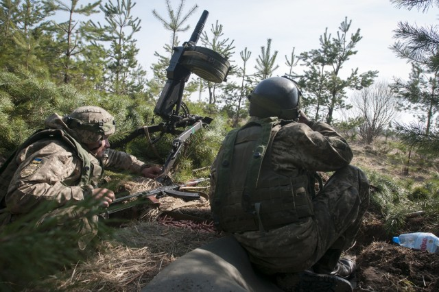 Two soldiers of the Ukrainian army's 1st Battalion, 28th Mechanized Infantry Brigade man an automatic grenade launcher while waiting for opposing force role players to attack their defensive line during a battalion wide defensive training operation at the Yavoriv Combat Training Center on the International Peacekeeping and Security Center, near Yavoriv, Ukraine, on March 29. The 1-28 battalion defense exercise was the culminating event for the unit's rotation through the CTC. During their time at the CTC, soldiers learned individual-, squad-, platoon- and company-level defensive tactics from their international partners in the Joint Multinational Training Group - Ukraine.