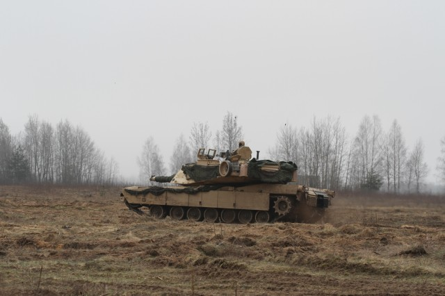 U.S. Soldiers from Company B, 1st Battalion, 68th Armored Regiment, 3rd Armored Brigade Combat Team, 4th Infantry Division, out of Fort Carson, Colo., hold their position in an M1A1 Abrams as a part of a combined exercise Savage Wolf with their Lithuanian counterparts as part of Operation Atlantic Resolve, April 4. The U.S. and Lithuanian Soldiers are split into two integrated teams and are given either an offensive role in taking an 'airfield' or defensive role to keep their position on the 'airfield'. The U.S. and our Allies and partners are making strides toward interoperability by continuously training together and implementing innovative solutions to common problems. Operation Atlantic Resolve is a U.S. led effort in Eastern Europe that demonstrates U.S. commitment to the collective security of NATO and dedication to enduring peace and stability in the region. (U.S. Army photo by Staff Sgt. Jill People)