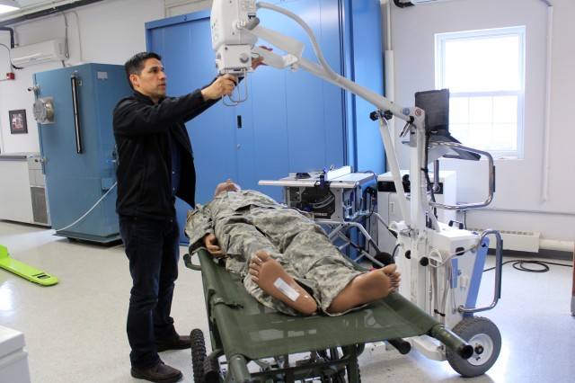 U.S. Army Medical Materiel Agency Equipment Specialist Diego Gomez-Morales demonstrates the new Portable Digital Radiography System (PDRS) that will replace two aging devices, including an X-ray generator and an accompanying computerized reader system. The PDRS combines these capabilities into a single lightweight X-ray unit intended for use by deployed medical, Special Operations and Mortuary Affair Army units. Photo by Ellen Crown, US Army Medical Materiel Agency.