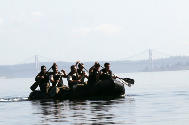 """Soldiers from 3rd Battalion, 1st Special Forces Group (Airborne), paddle through the Puget Sound during a competition as part of """"Dragon Week"""" held on Joint Base Lewis McChord, Wash., June 29. Dragon Week consisted of airborne operations, maritime operations, patrol lanes, a stress shoot, and medical evaluations to test readiness at the battalion level."""