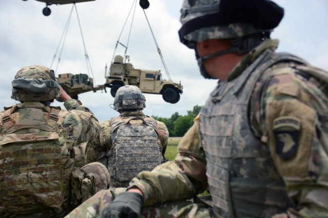 U.S. Army Soldiers from the 2nd Brigade Combat Team, 101st Airborne Division (Air Assault) watch as a CH-47 Chinook flown by Soldiers from the 101st Combat Aviation Brigade, 101st Airborne, sling loads the Tactical Control Node-Light at Fort Campbell, KY, Jun. 15, 2017. The training was part of the brigade preparation for the Network Integration Exercise at Fort Bliss, where they were the first light BCT to participate, July 5 - 6, 2017. The Tactical Communications Node was originally developed on five-ton Family of Medium Tactical Vehicles (FMTVs). The new Lite (L) versions are integrated onto Humvees, which can be sling-loaded from a helicopter for significantly increased agility and operational flexibility.