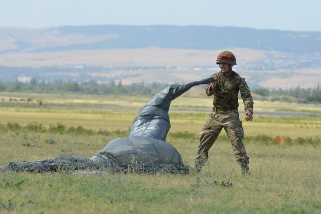 VAZIANI TRAINING AREA, Georgia - A British Soldier, Pvt. Christopher Kantorowicz, 2nd Battalion, Parachute Regiment (2nd PARA), 16th Air Assault Brigade, Colchester, England, twists the MC-6 model parachute to assist in managing it at the drop zone on Vaziani Training Area, Georgia, Aug. 7, 2017. The red tape signifies first-time jumpers. The 2nd PARA is currently in the Republic of Georgia to participate in Exercise Noble Partner. Noble Partner is a multinational, U.S. Army Europe-led exercise conducting home station training for the Georgian light infantry company designated for the NATO Response Force. (U.S. Army photo by Sgt. Shiloh Capers)