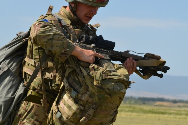 VAZIANI TRAINING AREA, Georgia - British soldier Pvt. Christopher Kantorowicz, 2nd Battalion, Parachute Regiment (2nd PARA), 16th Air Assault Brigade, Essex, England, treks to the collection point with full gear, at the drop zone on Vaziani Training Area, Georgia, Aug. 7, 2017. The red tape signifies first-time jumpers. The 2nd PARA is currently in the Republic of Georgia to participate in Exercise Noble Partner. Noble Partner is a multinational, U.S. Army Europe-led exercise conducting home station training for the Georgian light infantry company designated for the NATO Response Force. (U.S. Army photo by Sgt. Shiloh Capers)