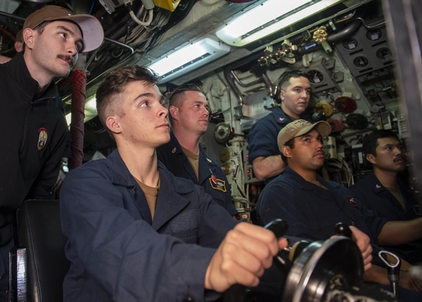 Electronics Technician (Navigation) Seaman Tyler Mcmillen, from Erie, Pennsylvania, stands watch as helmsman aboard the Los Angeles-class fast-attack submarine USS Chicago (SSN 721) in support of Valiant Shield 2020 on Sept. 14, 2020. Valiant Shield is a U.S.-only, biennial field training exercise (FTX) with a focus on integration of joint training in a blue-water environment among U.S. forces. This training enables real-world proficiency in sustaining joint forces through detecting, locating, tracking, and engaging units at sea, in the air, on land, and in cyberspace in response to a range of mission areas. MC1 Derek Harkins/US Navy.