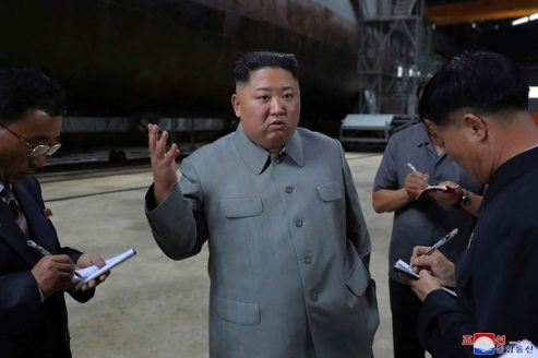 In this undated photo provided on Tuesday, July 23, 2019, North Korean leader Kim Jong Un, center, speaks while inspecting a newly built submarine to be deployed soon, at an unknown location in North Korea. (Korean Central News Agency/Korea News Service via AP)