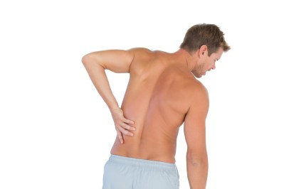 Man rubbing his back because of a back pain on white background