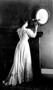 Helen Keller near roses and a mirror. By White, 1907.