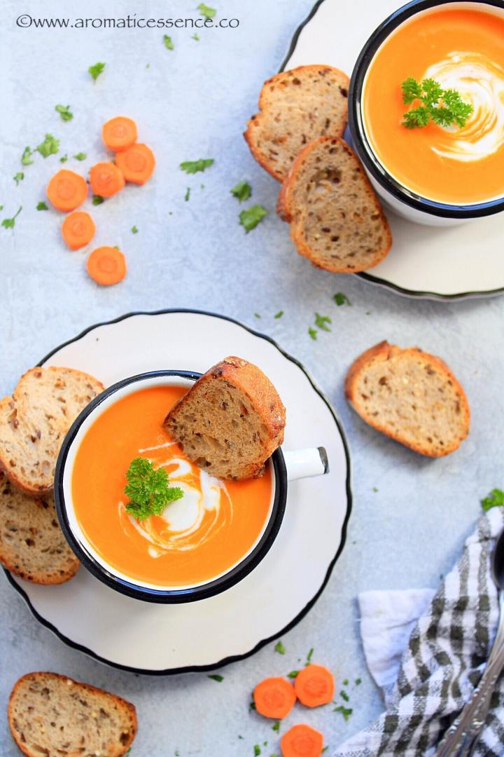 Vegan Carrot Ginger Soup served in white enamel mugs with crusty bread
