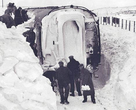 Workmen digging to free a train which was trapped in deep drifts on Dava Moor between Forres and Grantown on Spey in Scotland.