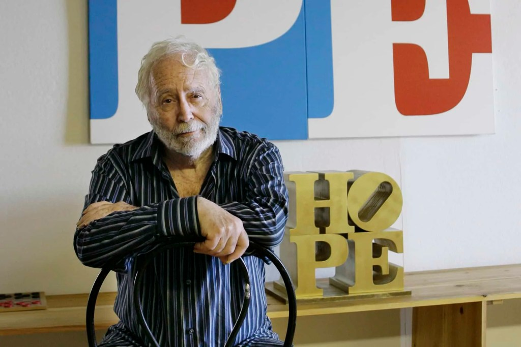 Robert Indian sits in front of one of his artworks Art World Roundup