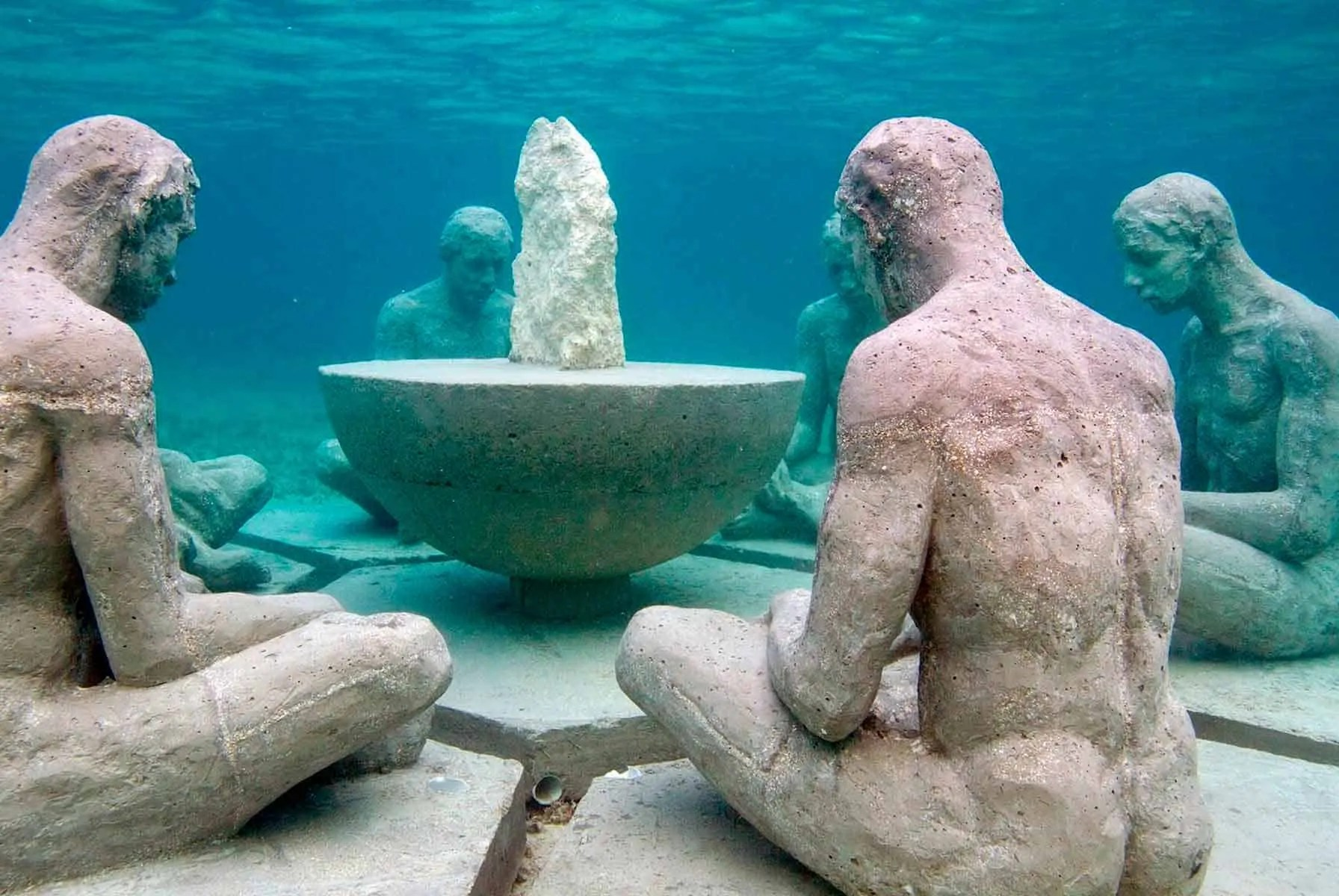 sculpture of seated men in a circle underwater