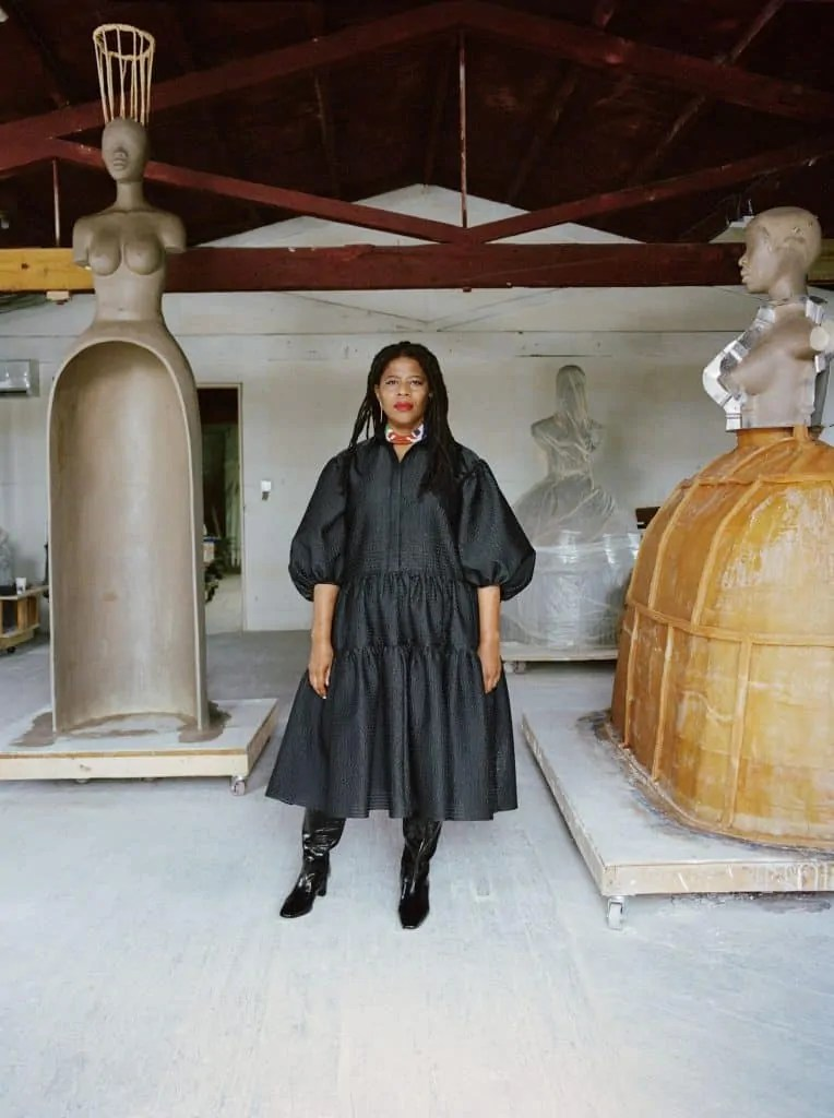 Simone Leigh, wearing a black dress, stands before a number of her artworks. Art World Roundup